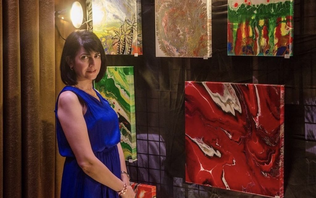 Photo of Zahra Zlayer and her artwork