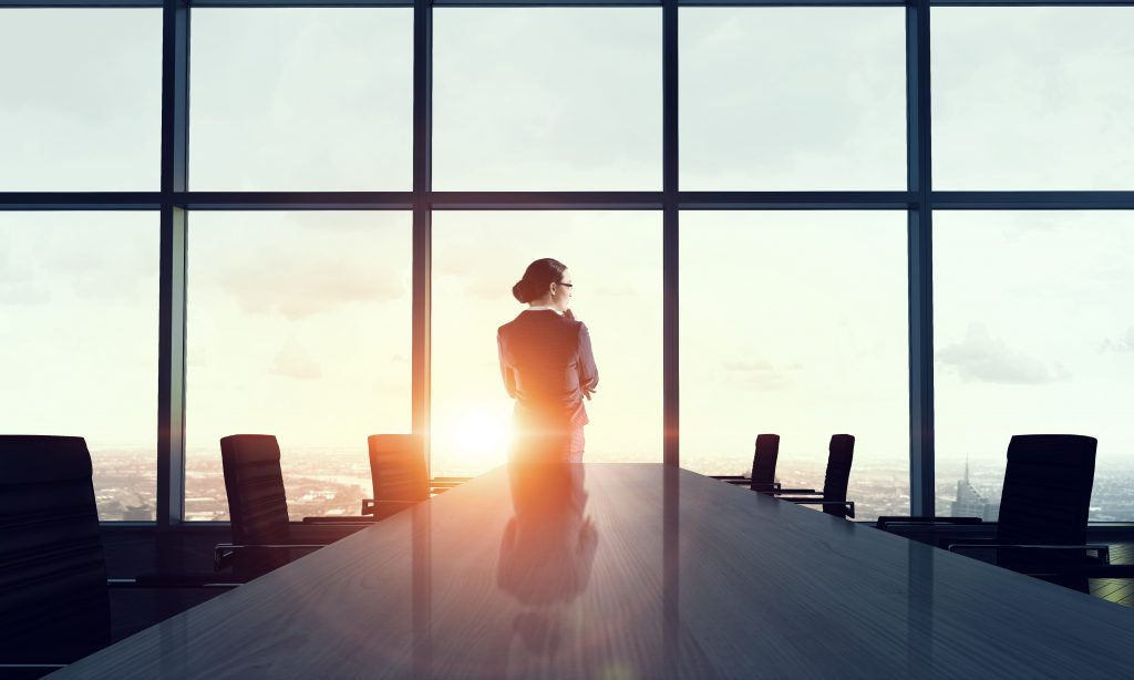 Woman in suit at head of empty boardroom table looking over the city